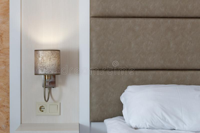 Modern white color tone bedroom, white pillow and bed linen, modern lamp turned on royalty free stock image