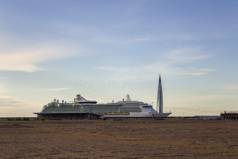 Modern white cruise liner on the background of a skyscraper under a clear blue sky, view from the desert. A modern white cruise liner on the background of a stock photos