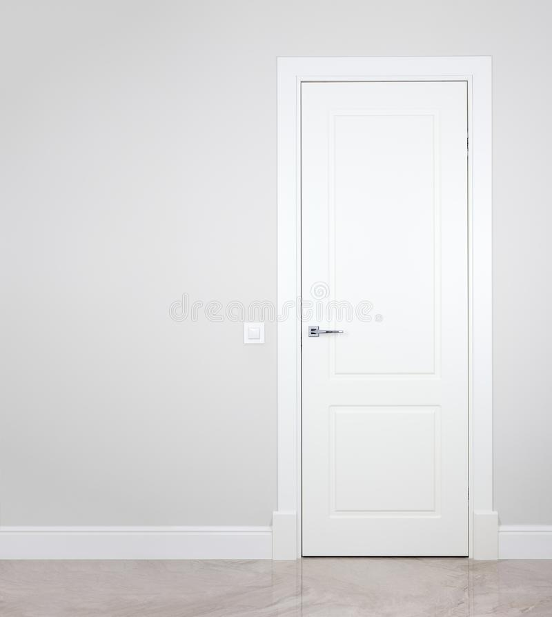 Modern white door. Grey wall with free space. Minimalist. Bright interior stock photography