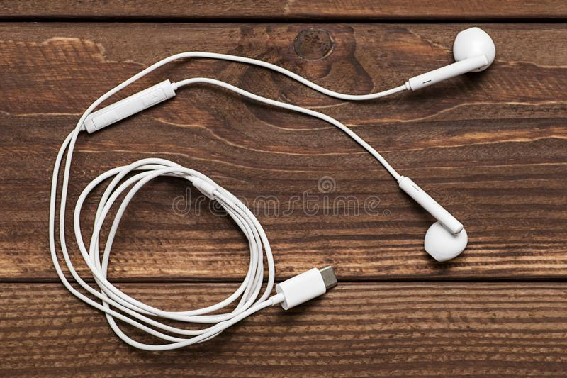 Modern white earphone, white in ear headphone on wooden table. White earphones over wooden board royalty free stock image