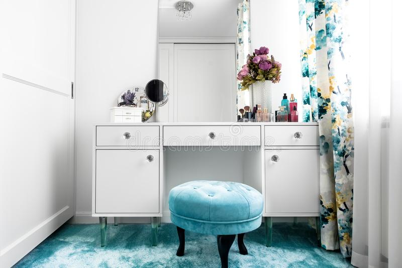 white, feminine dressing room with minimalist vanity table and mirror stock photography