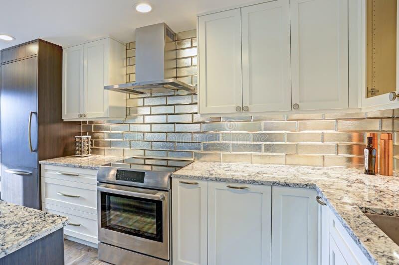 Modern white kitchen design with silver backsplash stock images