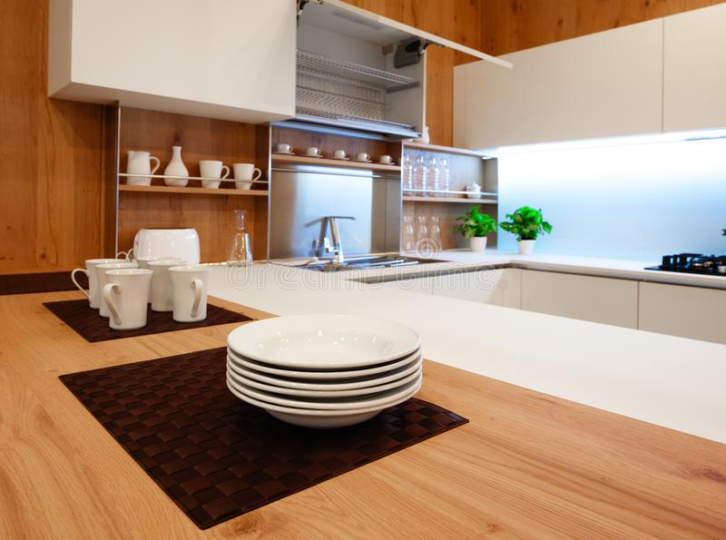 Modern white kitchen with wooden and white details, minimalistic interior design stock photo