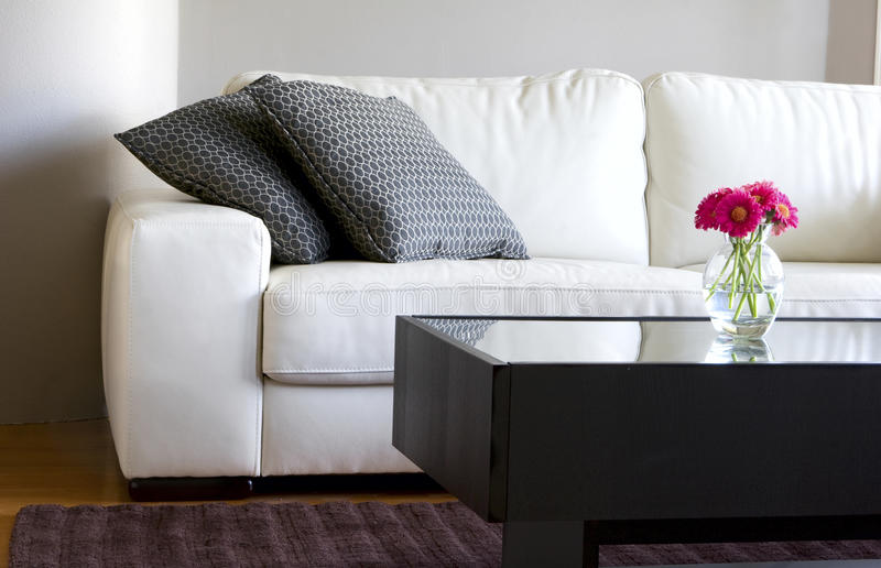 Modern white living room with pink daisies. Modern white living room with vase of pink daisies stock photos
