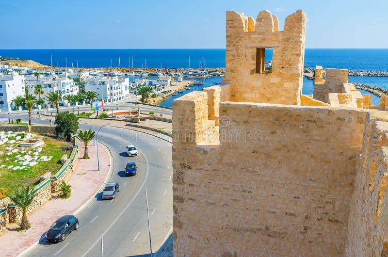 The towers of Ribat in Monastir. The modern white neighborhood and yacht port behind the old tower of Ribat, Monastir, Tunisia stock photo