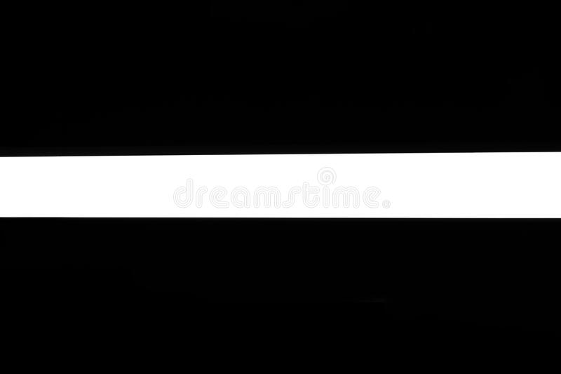 Modern white neon wall or ceiling lamp in the form of a long stripe in a dark room. Horizontal abstract geometric shape and line. On a black background stock images