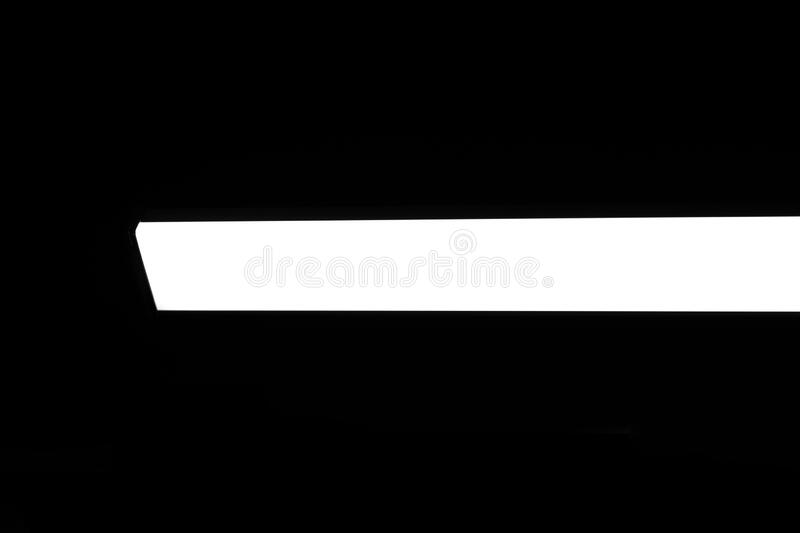 Modern white neon wall or ceiling lamp in the form of a long stripe in a dark room. Horizontal abstract geometric shape and line. On a black background stock photography