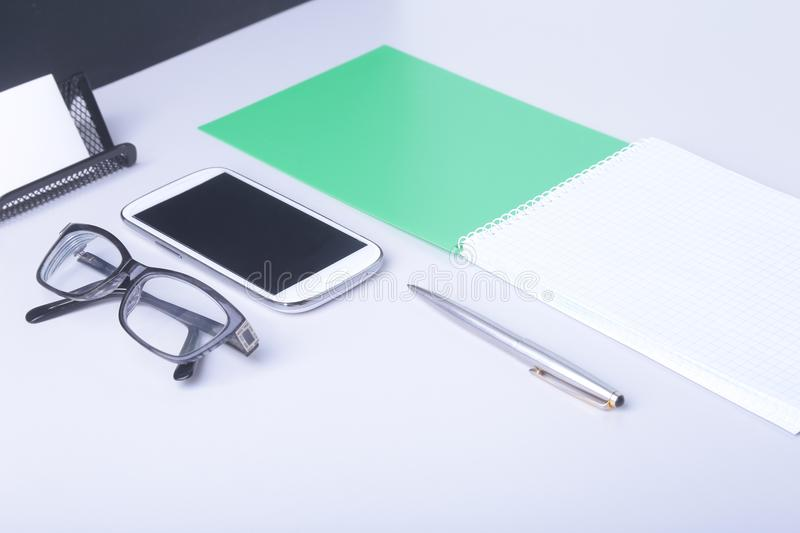 Modern white office desk table with laptop, smartphone and other supplies. Blank notebook page for input the text in the royalty free stock photos