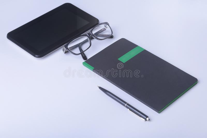 Modern white office desk table with laptop, smartphone and other supplies. Blank notebook page for input the text in the stock photo