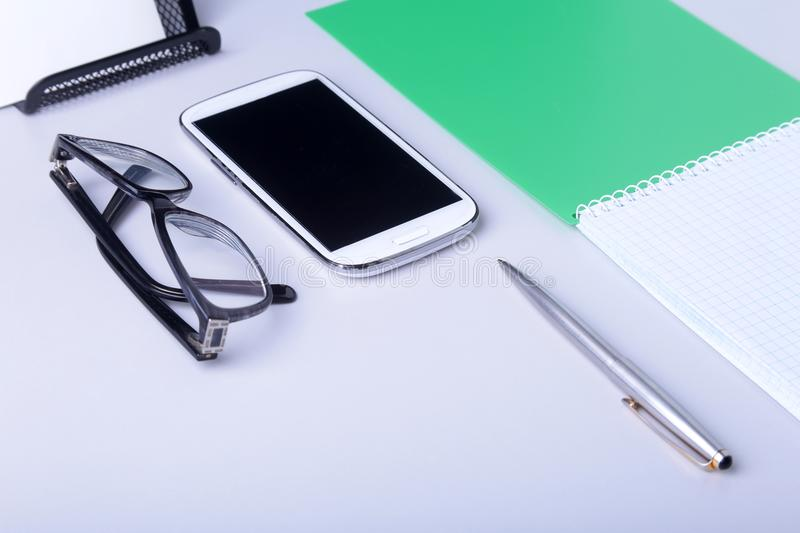 Modern white office desk table with laptop, smartphone and other supplies. Blank notebook page for input the text in the stock photos