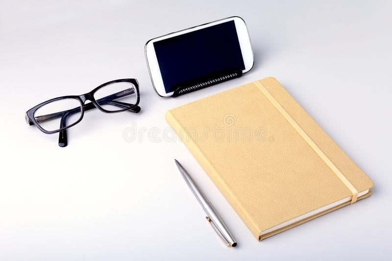 Modern white office desk table with laptop, smartphone and other supplies. Blank notebook page for input the text in the royalty free stock image