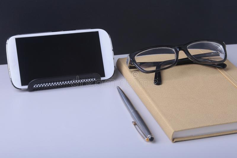 Modern white office desk table with laptop, smartphone and other supplies. Blank notebook page for input the text in the stock image