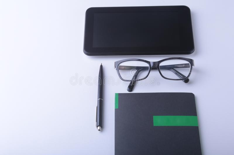 Modern white office desk table with laptop, smartphone and other supplies. Blank notebook page for input the text in the royalty free stock photography