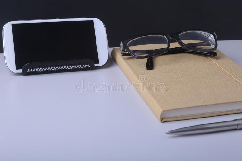 Modern white office desk table with laptop, smartphone and other supplies. Blank notebook page for input the text in the stock images