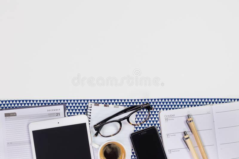 Modern white office desk table with a notebook diary, pens, eyeglasses, tablet, smartphone and cup of coffee. Top view with copy. Space, flat lay royalty free stock photo