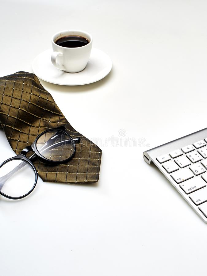 Modern white office desk top table with a cup of coffee, Necktie and other supplies. Top view with copy space. Modern white office desk top table with a cup of stock photos