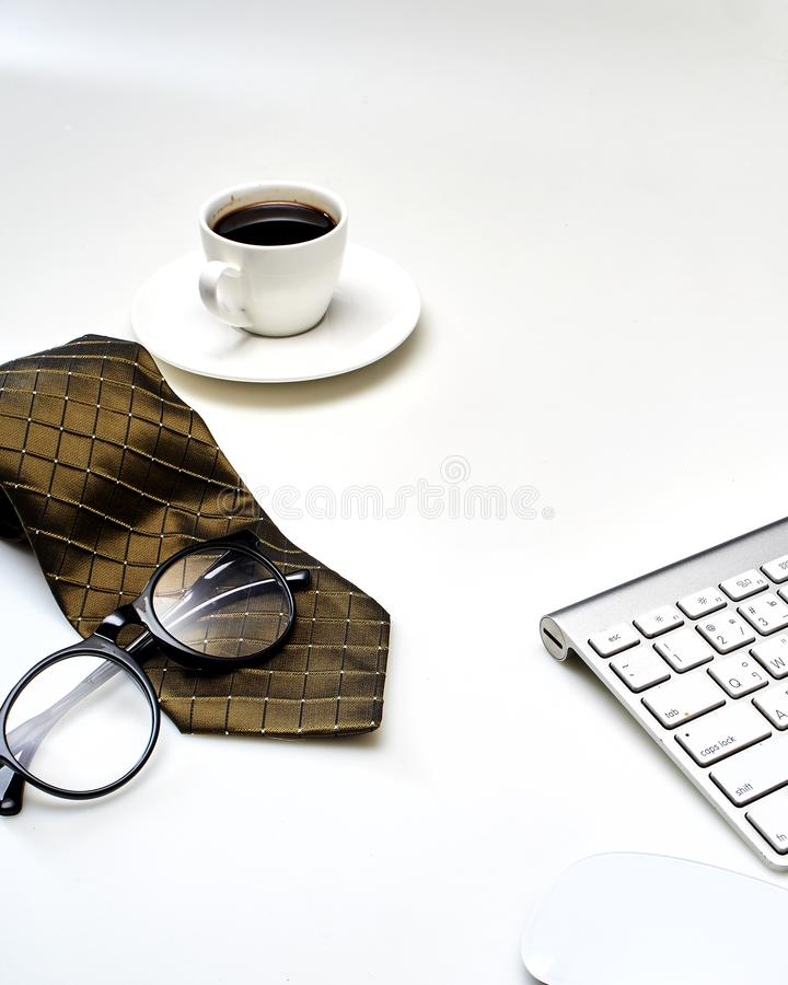 Modern white office desk top table with a cup of coffee, Necktie  and other supplies. Top view with copy space. Modern white office desk top table with a cup of royalty free stock image