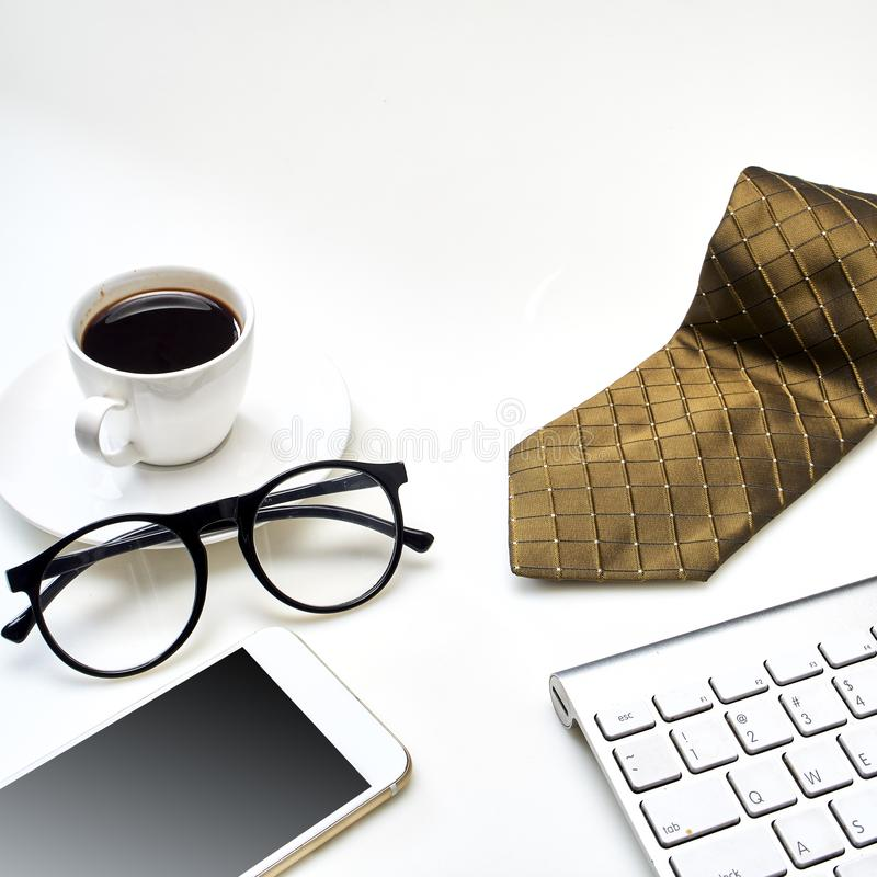 Modern white office desk top table with a cup of coffee, Necktie  and other supplies. Top view with copy space. Modern white office desk top table with a cup of stock photography