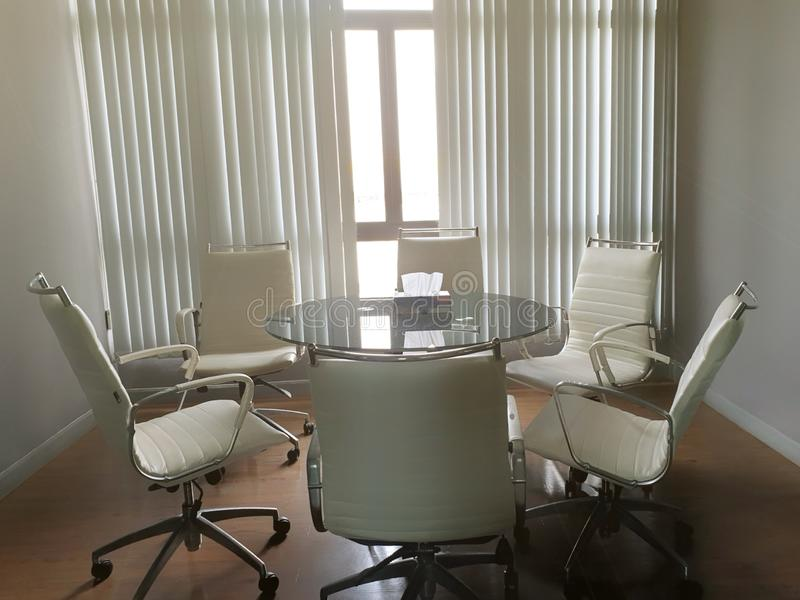 Modern white office of table and chairs with sun shining in meeting room stock photography