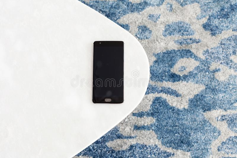 Modern white stool made of artificial stone stands on a carpet with fine nap, a top view. The mobile phone lies on a new chair. Composition, texture, color royalty free stock image