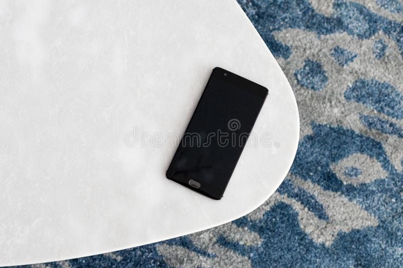 Modern white stool made of artificial stone stands on a carpet with fine nap, a top view. The mobile phone lies on a new chair. Composition, texture, color stock photo