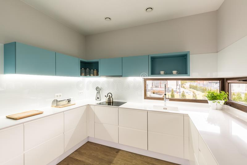 Modern white and turquoise kitchen. Led illuminated, modern, white and turquoise kitchen interior with cupboards, induction stove and corner windows stock photography