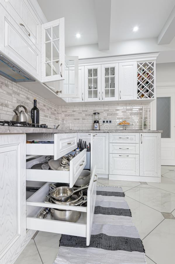 Modern white wooden kitchen interior. Interior of modern white wooden kitchen in luxury home, some drawers are open stock photography
