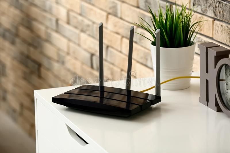 Modern wi-fi router on light commode near brick wall stock image