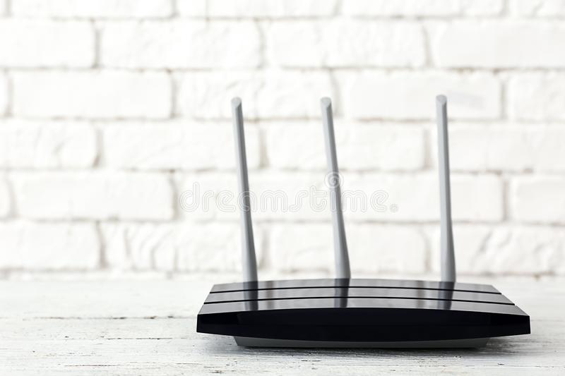Modern wi-fi router on light table near brick wall stock image