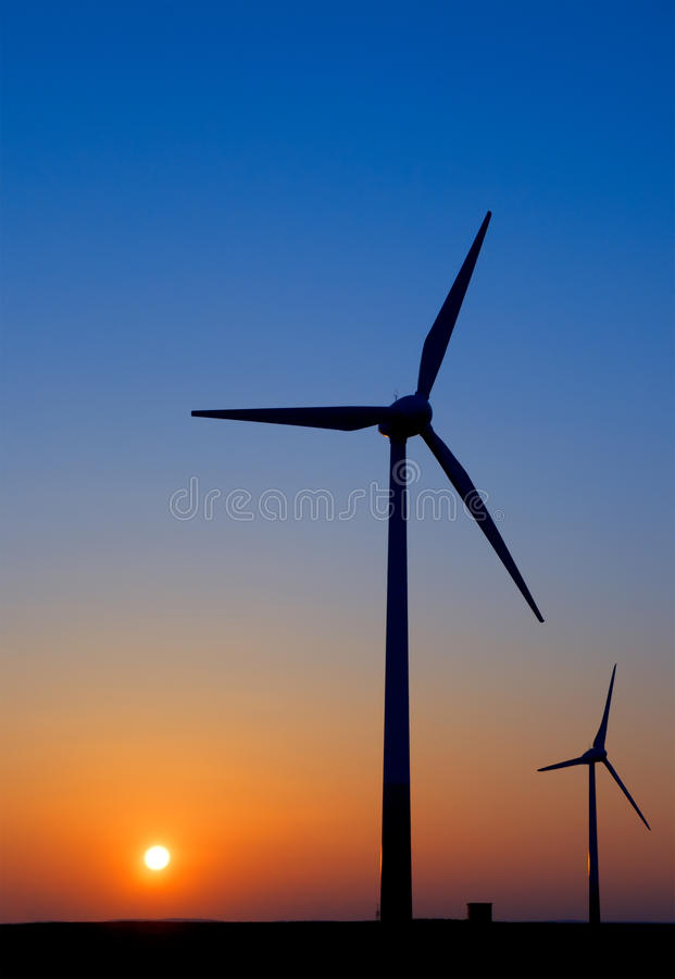 Modern windmills against sunset royalty free stock photography