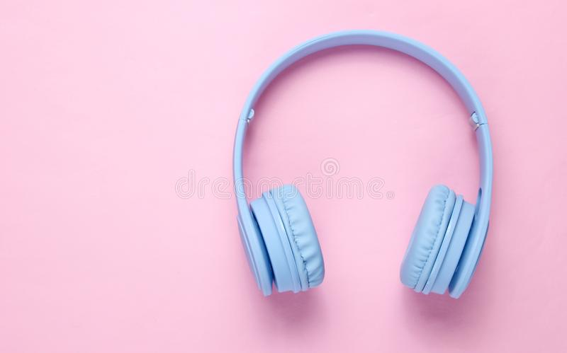 Modern wireless blue headphones. On a pink pastel background. Top view. Copy space royalty free stock photos