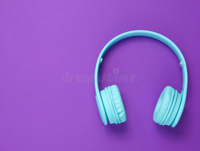 Modern wireless blue headphones. On purple background. Top view. Copy space stock photos