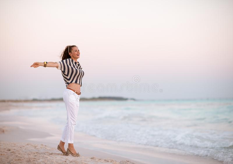 Modern woman on beach at sunset rejoicing royalty free stock image