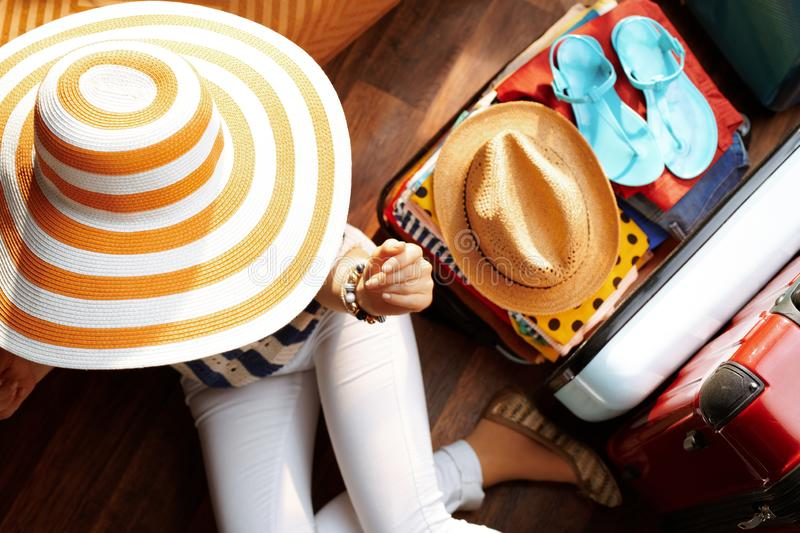 Modern woman with big summer hat packing for summer holiday. Upper view of modern woman in white pants and striped blouse with big summer hat near open travel royalty free stock photo