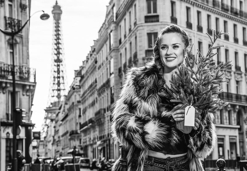 Modern woman with Christmas tree in Paris looking into distance. Boiling hot trendy winter in Paris. Portrait of smiling modern woman with Christmas tree in stock photo