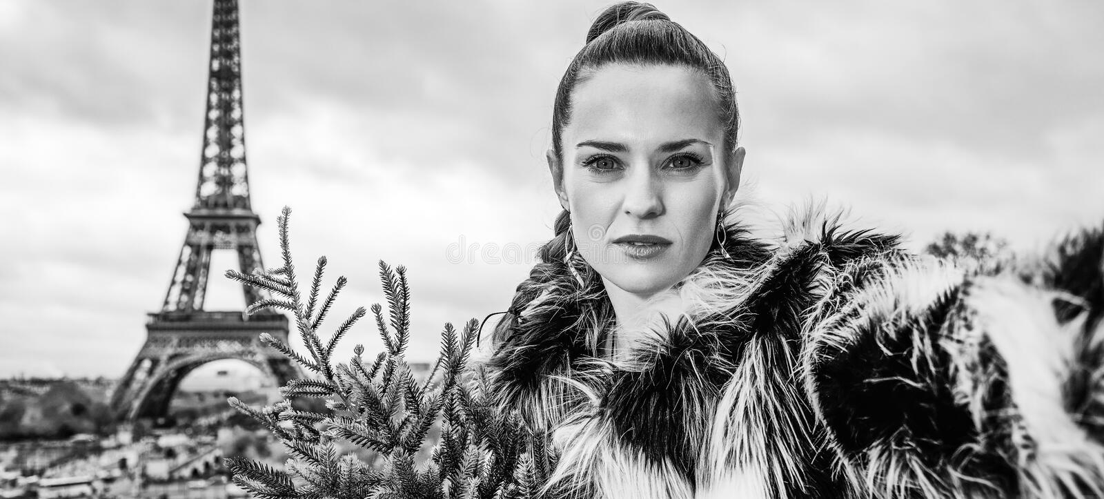 Modern woman with Christmas tree taking selfie in Paris. The Party Season in Paris. modern woman with Christmas tree in fur coat in the front of Eiffel tower in royalty free stock photos