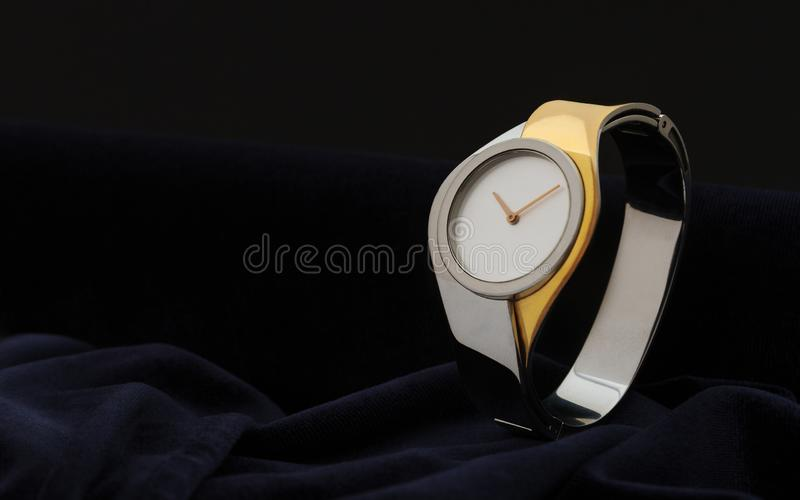 Modern woman gold and silver Wristwatch on dark velvet fabric background stock photography