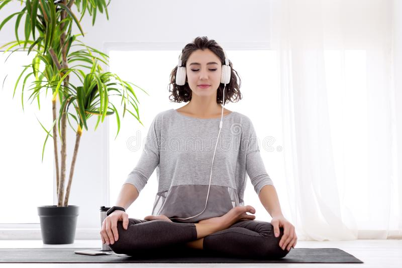 Modern woman with headphones sitting in yoga lotus posture. Slender female folded crossed legs in lotus position. Young athletic woman in fitness tracker and royalty free stock photo