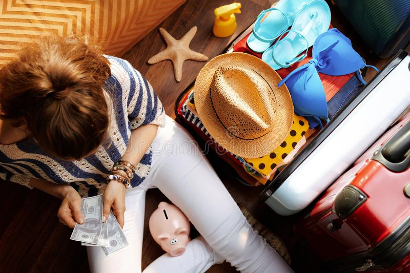 Modern woman with piggy bank counts summer budget money. Upper view of modern woman in white pants and striped blouse with piggy bank counts summer budget money stock image