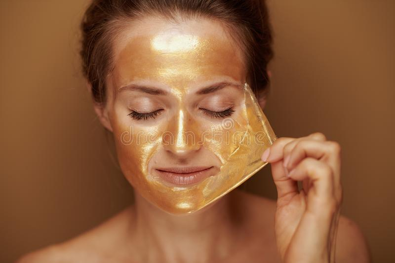 Modern woman removing golden mask against beige background stock photography