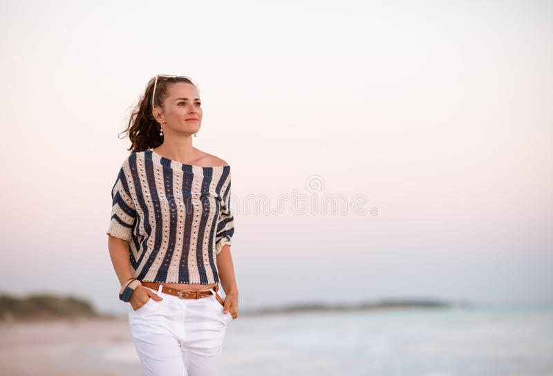 Modern woman on seacoast at sunset looking into distance royalty free stock images