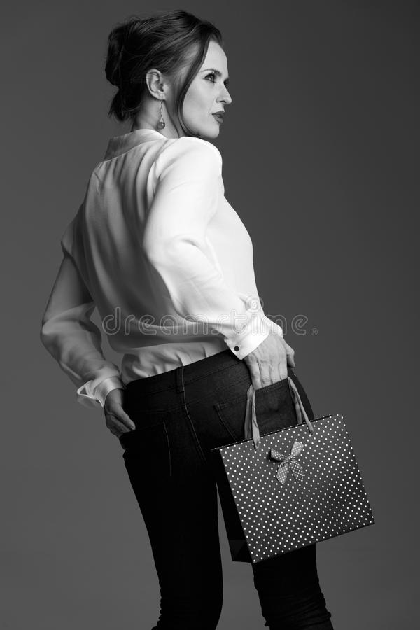 Download Modern Woman With Shopping Bag Posing Against Grey Background Stock Image