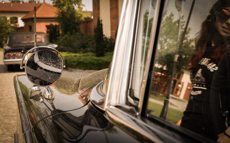 Old american car`s details with modern woman`s reflection. Beautiful old timer. stock photos