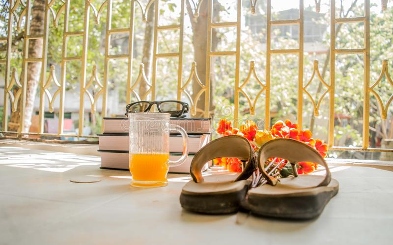 Modern women holiday essential for sunday summer time weekend activities on wooden table. Sunglasses placed over Books, flip flops. Cocktail glass and flower royalty free stock photos