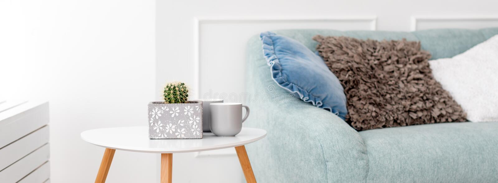 Modern wooden coffee table and cozy sofa with pillows. Living room interior and simple modern home decor concept. royalty free stock images