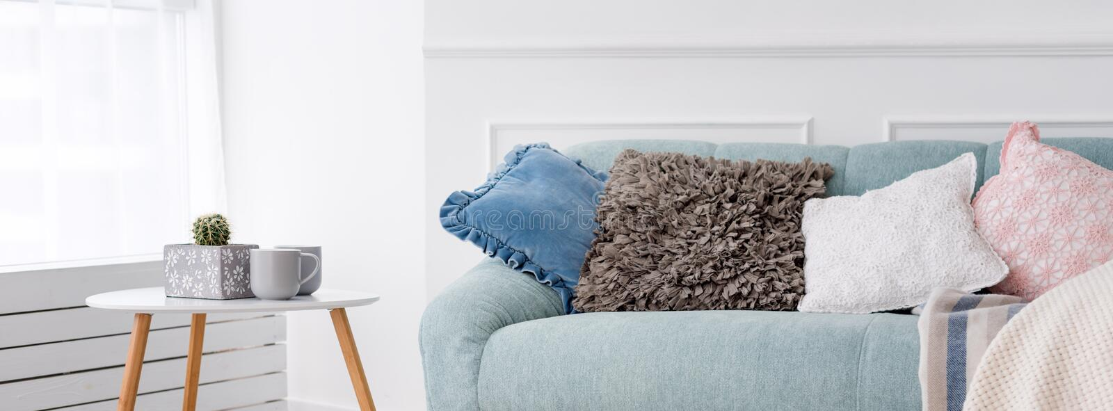 Modern wooden coffee table and cozy sofa with pillows. Living room interior and simple modern home decor concept. stock images