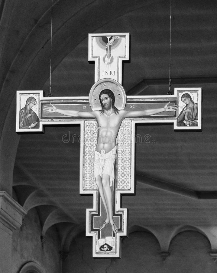 Modern wooden crucifix hanging in the central nave of the Abbey. Carceri, Italy - April 2, 2018: Modern wooden crucifix hanging in the central nave of the Abbey royalty free stock images