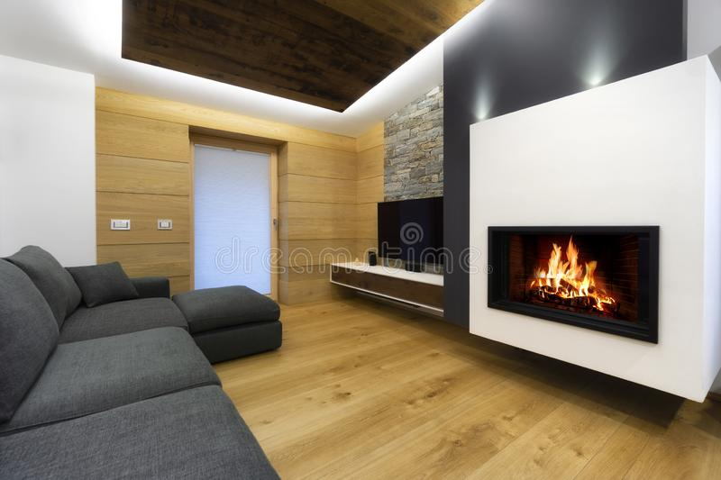 Modern wooden living room interior with sofa and fireplace stock photography