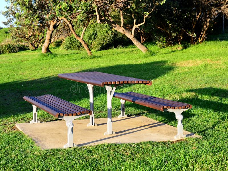 Modern Wooden Park Bench and Table. A modern wooden slat park bench and picnic table, mounted in a green grassy park, in early morning oblique light royalty free stock image