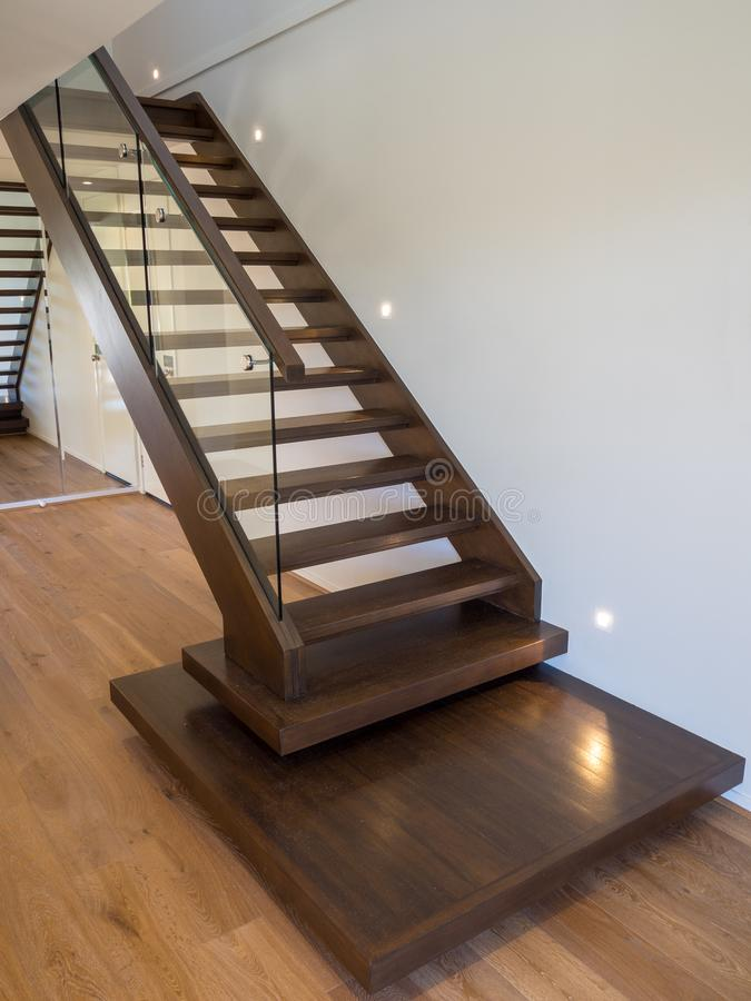 Modern wooden staircase with glass balustrade and mirror on back wall royalty free stock photo